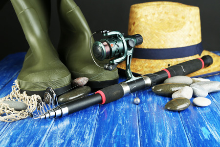 Fishing rod, gumboots and hat on wooden table close-up photo