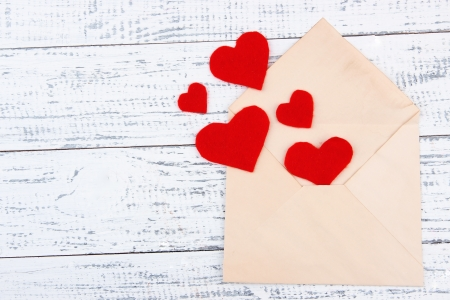 old envelope: Beautiful old envelope with decorative hearts on wooden background