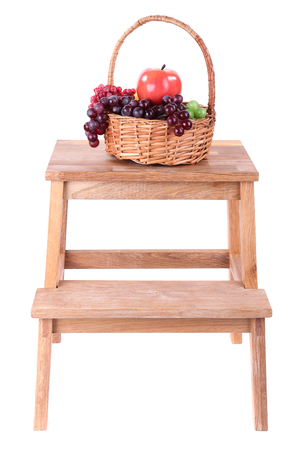 Wicker basket with fruits, on small wooden ladder, isolated on white photo