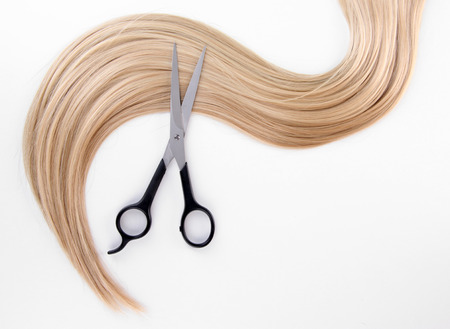 Long blond hair and scissors isolated on white photo