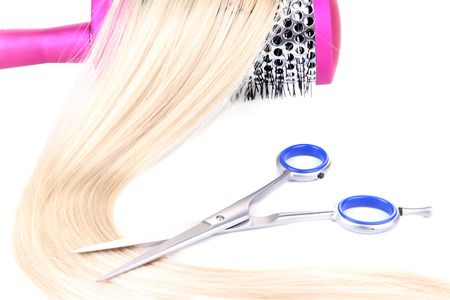 Long blond hair with hairbrush and scissors isolated on white photo