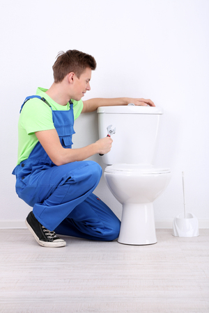 Plumber with toilet plunger on light background photo