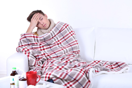 Guy wrapped in plaid sitting on sofa is ill Stock Photo - 26396888