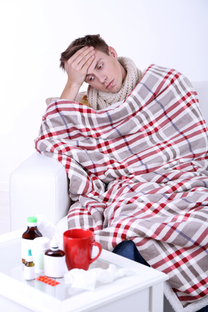 Guy wrapped in plaid sitting on sofa is ill Stock Photo - 26396889