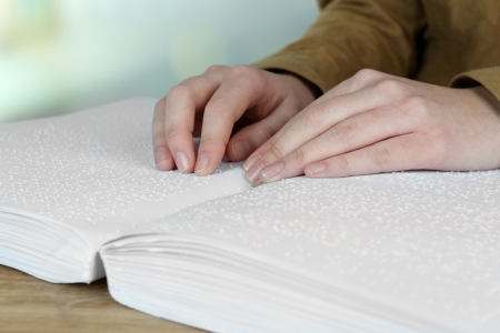 Blind woman read book written in Braille photo