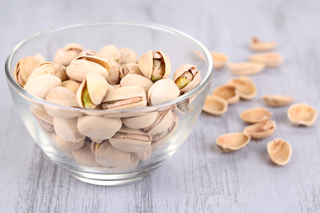 Pistachio nuts in glass bowl on wooden background photo