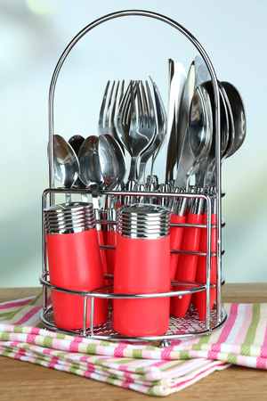 Kitchen cutlery in metal stand on wooden table on bright background photo