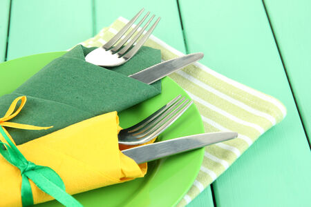 Forks and knives wrapped in green and yellow paper napkins, on color wooden background photo