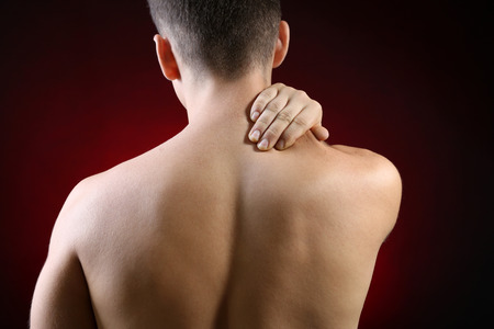 Young man with neck pain, on red background photo