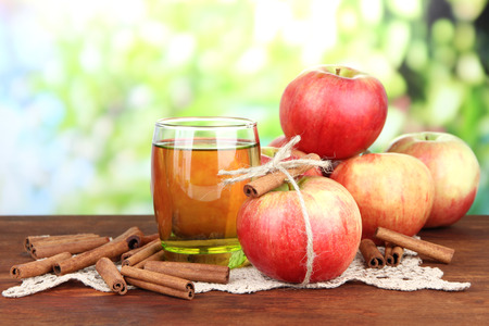 Ripe apples with with cinnamon sticks and glass of  apple drink  on  wooden table, on bright background photo