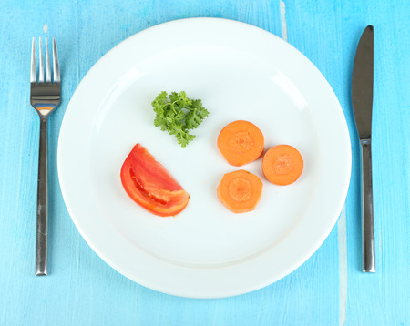 Small portion of food on big plate on wooden table close-up Stock Photo