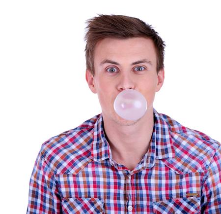 goma de mascar: Joven soplando burbujas de goma de mascar aisladas en blanco Foto de archivo