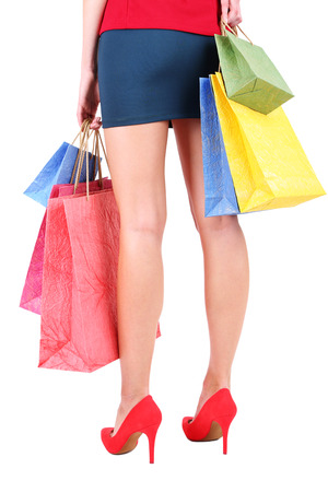 Female in red shoes holding shopping bags isolated on white photo