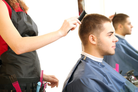 Beautiful girl hairdresser cut guy in beauty salon  photo