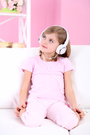 Little girl listening music sitting on sofa in room photo