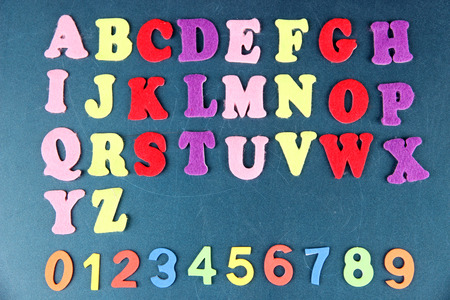 English alphabet and numbers on school desk background photo