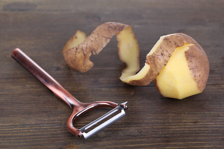 Peeler and fresh potato on wooden background photo