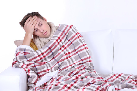 Guy wrapped in plaid sitting on sofa is ill Stock Photo - 26397024