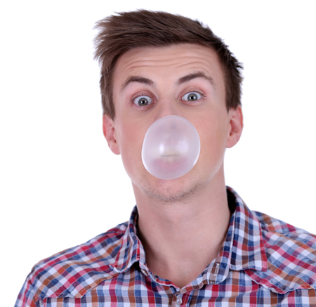 Young man blowing bubble of chewing gum isolated on white photo