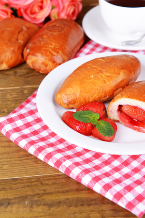 Fresh baked pasties with strawberries on plate on table close-up photo