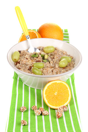 eat right: Useful oatmeal in bowl with fruit isolated on white