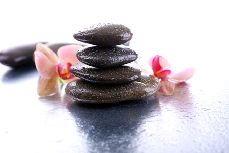 Composition with beautiful blooming orchid with water drops and spa stones, on light  photo