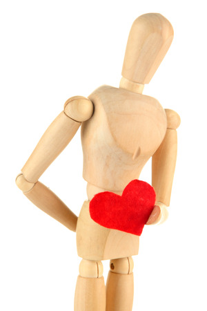 Wooden mannequin holding red heart isolated on white photo