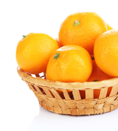 Ripe sweet tangerines in wicker basket, isolated on white photo