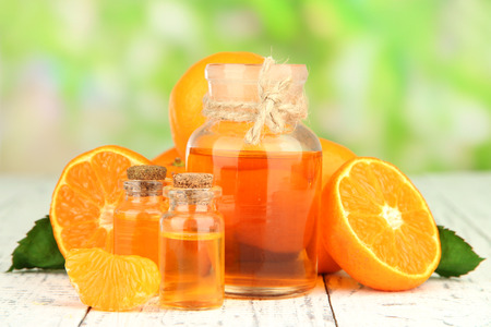 Tangerine essential oil and tangerines on wooden table, on nature background