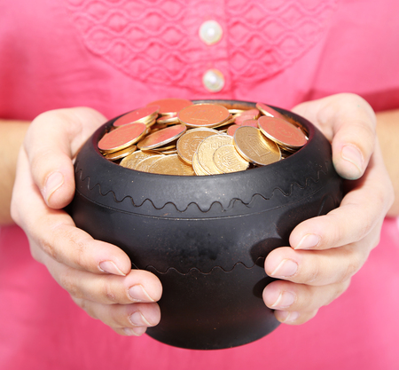 Ceramic pot with golden coins in female hands, isolated on white  photo
