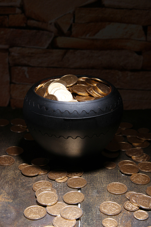 Golden coins in ceramic pot, on wooden table on dark  photo