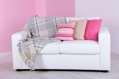 White sofa in room on pink wall