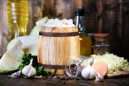Composition with fresh and marinated cabbage (sauerkraut) in wooden barrel, on wooden table  Stock Photo