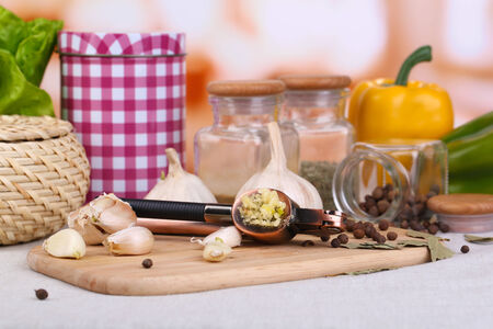 Composition with garlic press, fresh garlic and glass jars with spices on wooden table, on bright   photo
