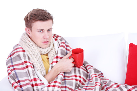 Guy wrapped in plaid lies on sofa on white background Stock Photo - 26375711