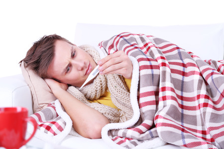 Guy wrapped in plaid lies on sofa is ill Stock Photo - 26375713