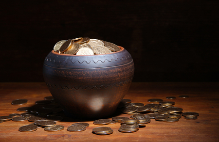 coin toss: Golden coins in ceramic pot, on wooden table on dark  Stock Photo