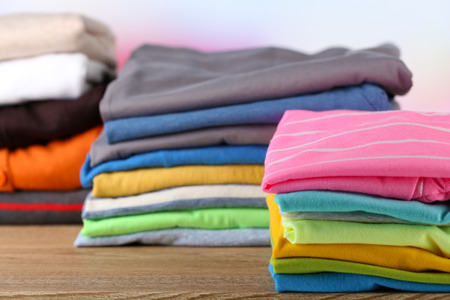Stack of colorful clothes, on light  photo