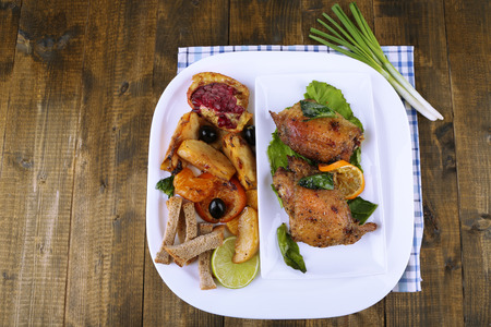 Homemade fried chicken drumsticks with vegetables on plate, on wooden  Stock Photo - 25737872