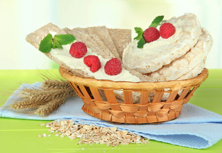 Tasty crispbread with berries in wicker basket, on green table photo