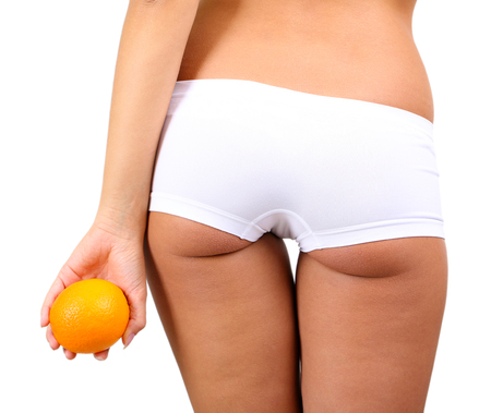 fatness: Beautiful young woman with orange on grey