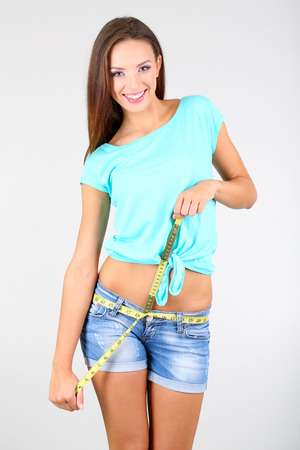 Beautiful young woman measuring her body with tape on grey background photo