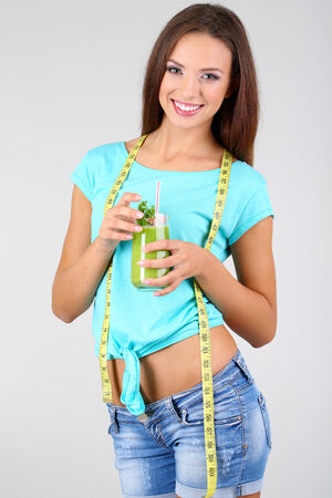 Beautiful girl with fresh juice and measuring tape on grey background photo