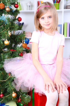 Little girl sitting on big present box near Christmas tree in room photo