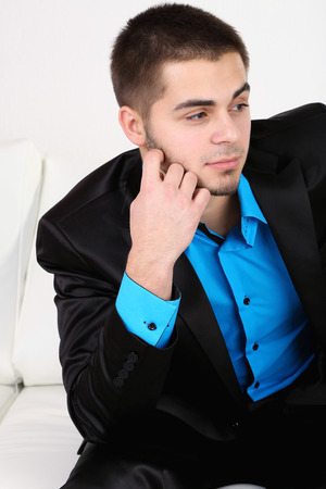 Handsome young man sitting on sofa on light background Stock Photo - 26375937