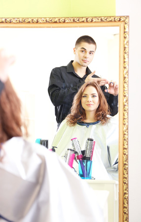 Young man hairdresser makes hairstyle girl in beauty salon  photo