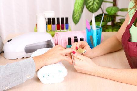 manicurist: Girl manicurist doing manicure for man in beauty salon  Stock Photo