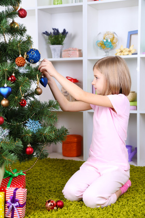 Little girl decorating Christmas tree in room photo