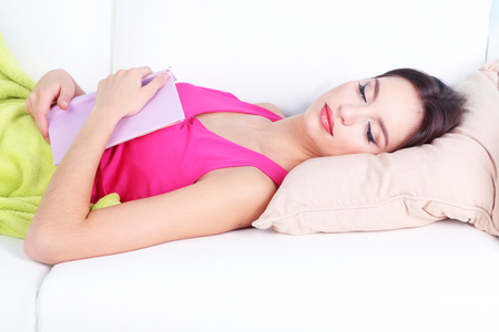 Beautiful young woman sleeping with book on sofa close up photo