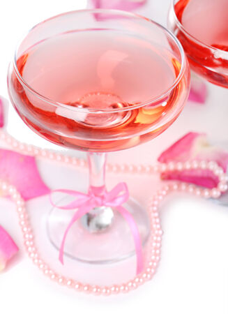 Composition with pink sparkle wine in glasses and rose petals isolated on white photo